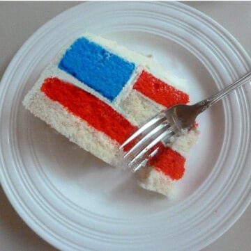 slice of american flag style cake on white platter with fork