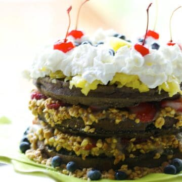 Banana split waffle cake with alternating layers of chocolate Belgian waffle and strawberries with peanuts, topped with whipped cream and maraschino cherries.