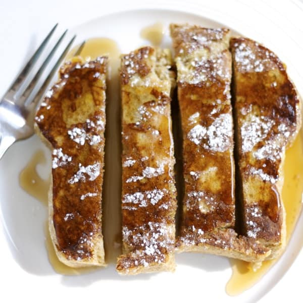 One slice of french toast drizzled in maple syrup, garnished with powdered sugar and cut in to four strips on a white plate from bird's eye view.