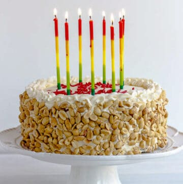 side view of italian rum cake with tall candles on white cake platter with pedestal