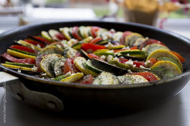 pan with sliced vegetables including eggplant, squash, zucchini and tomato