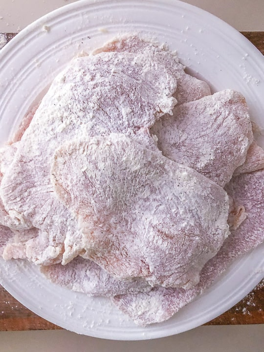 plate of flour coated sliced chicken breast