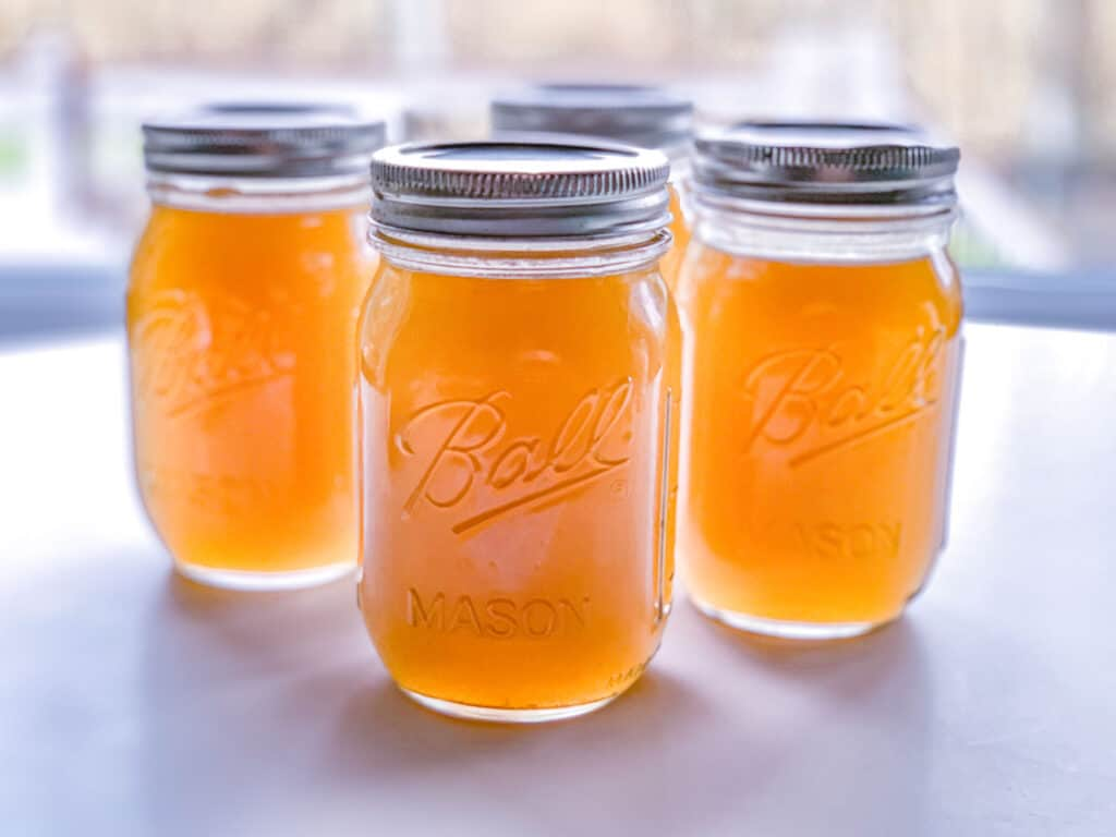 front view of pint sized glass jars filled with fresh chicken stock