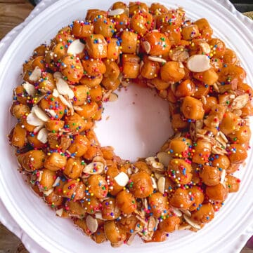 overhead view of struffoli arranged like a wreath on white dinner plate
