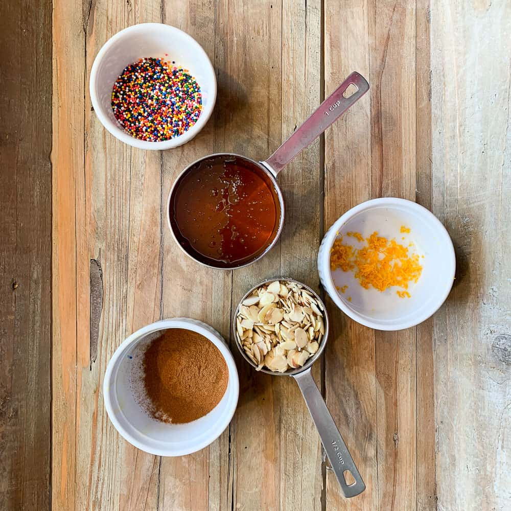 overhead view of ingredients for honey coating of struffoli (colored sprinkles, honey, cinnamon, nuts and orange zest)