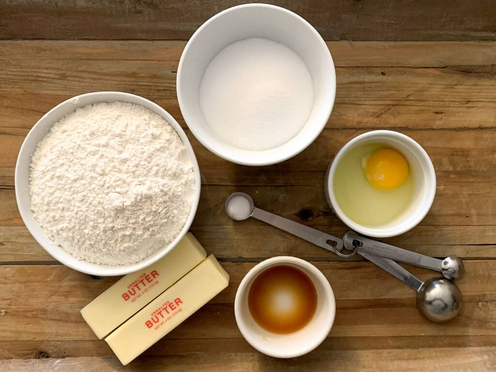 overhead view of sugar cookie dough ingredients including flour, butter, sugar, egg, salt, and vanilla extract