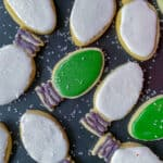 overhead view of sugar cookies shaped like Christmas tree lights on black tray