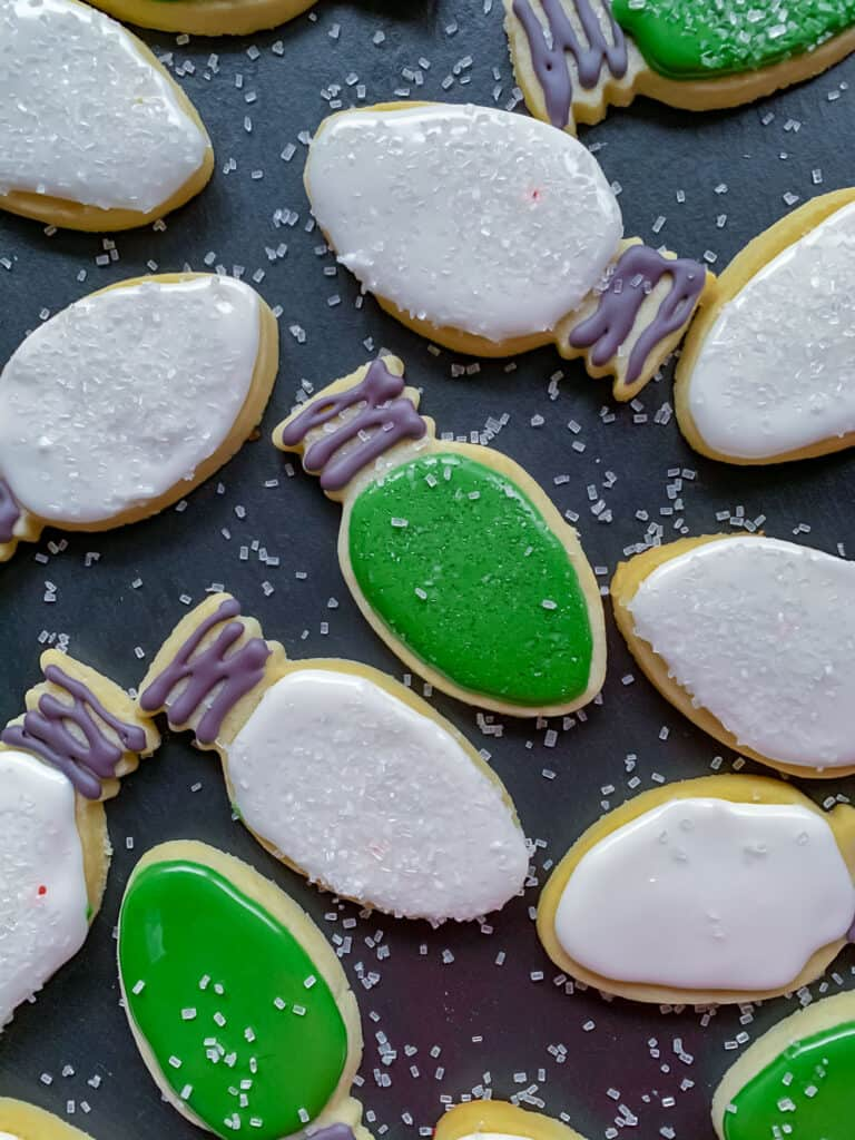 Overhead photo of sugar cookies shaped like christmas tree bulbs, iced with green or white icing and sprinkled with coarse sugar on black tray