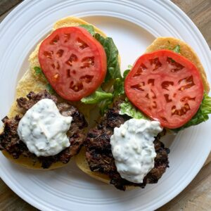 overhead view of open face gyro burgers on bun with tomato lettuce and tzatziki sauce