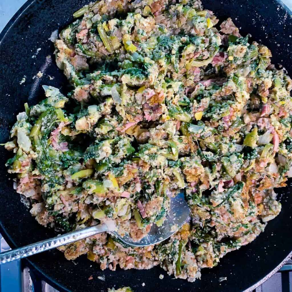 overhead view of utica greens in black pan with serving spoon