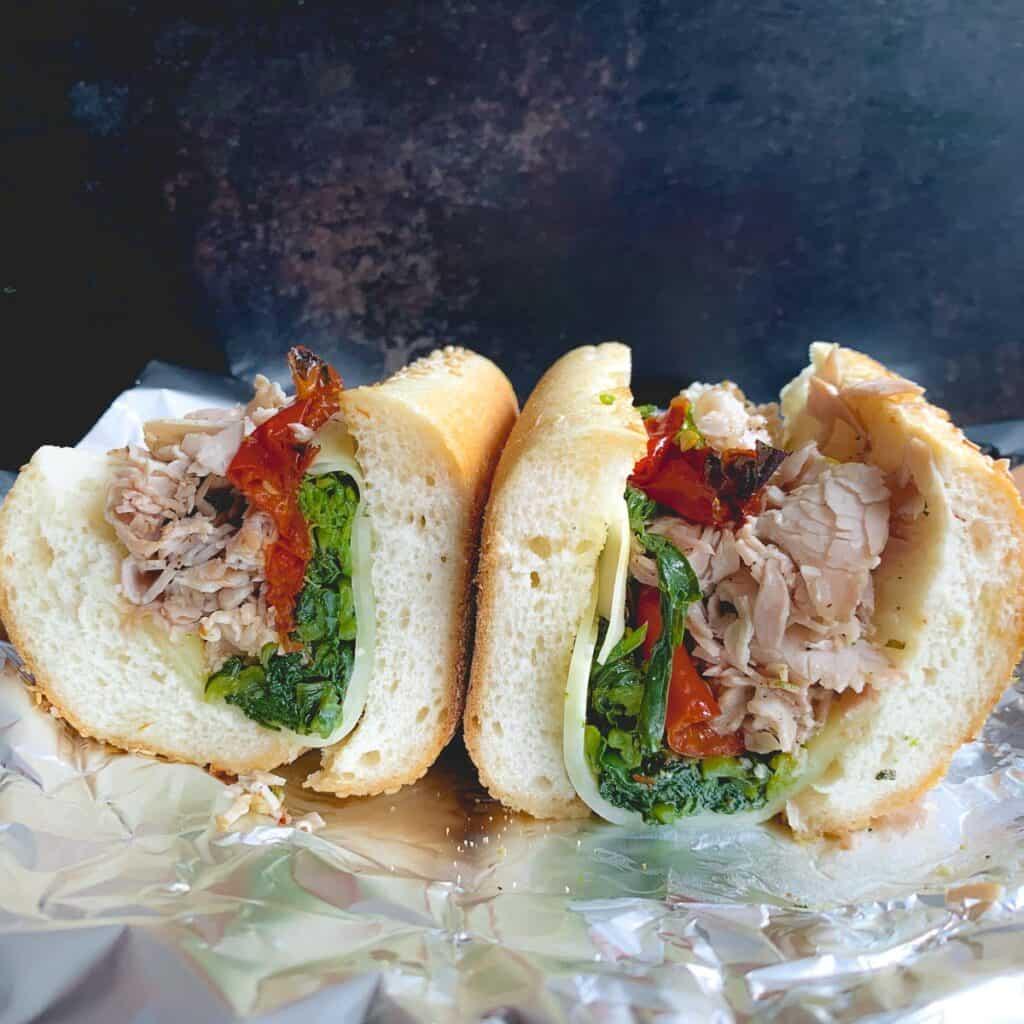 Philadelphia roast pork sandwich cut in half cross section view on aluminum foil