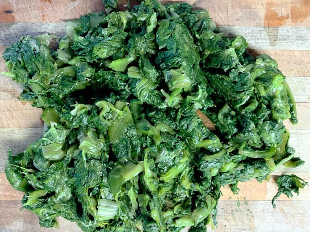 cooked escarole on wooden board