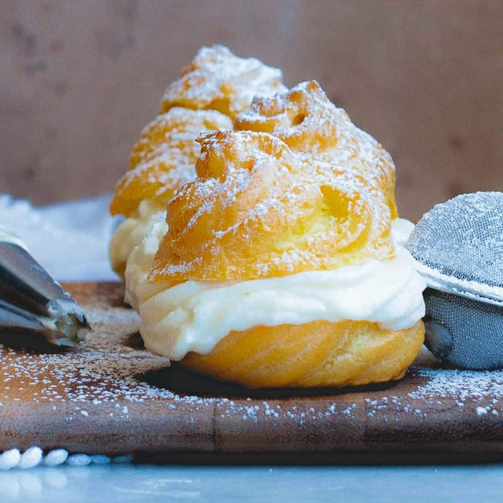 side view of italian cream puff with ricotta cheese and powdered sugar
