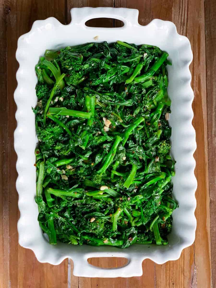 overhead view of cooked broccoli rabe in white casserole dish on wooden background