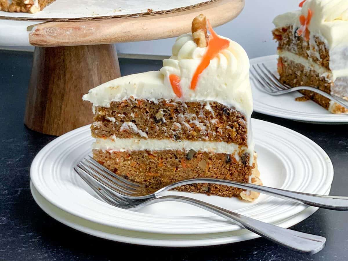 side view of carrot cake slice on white dish with forks. How to Make the Best Carrot Cake Ever