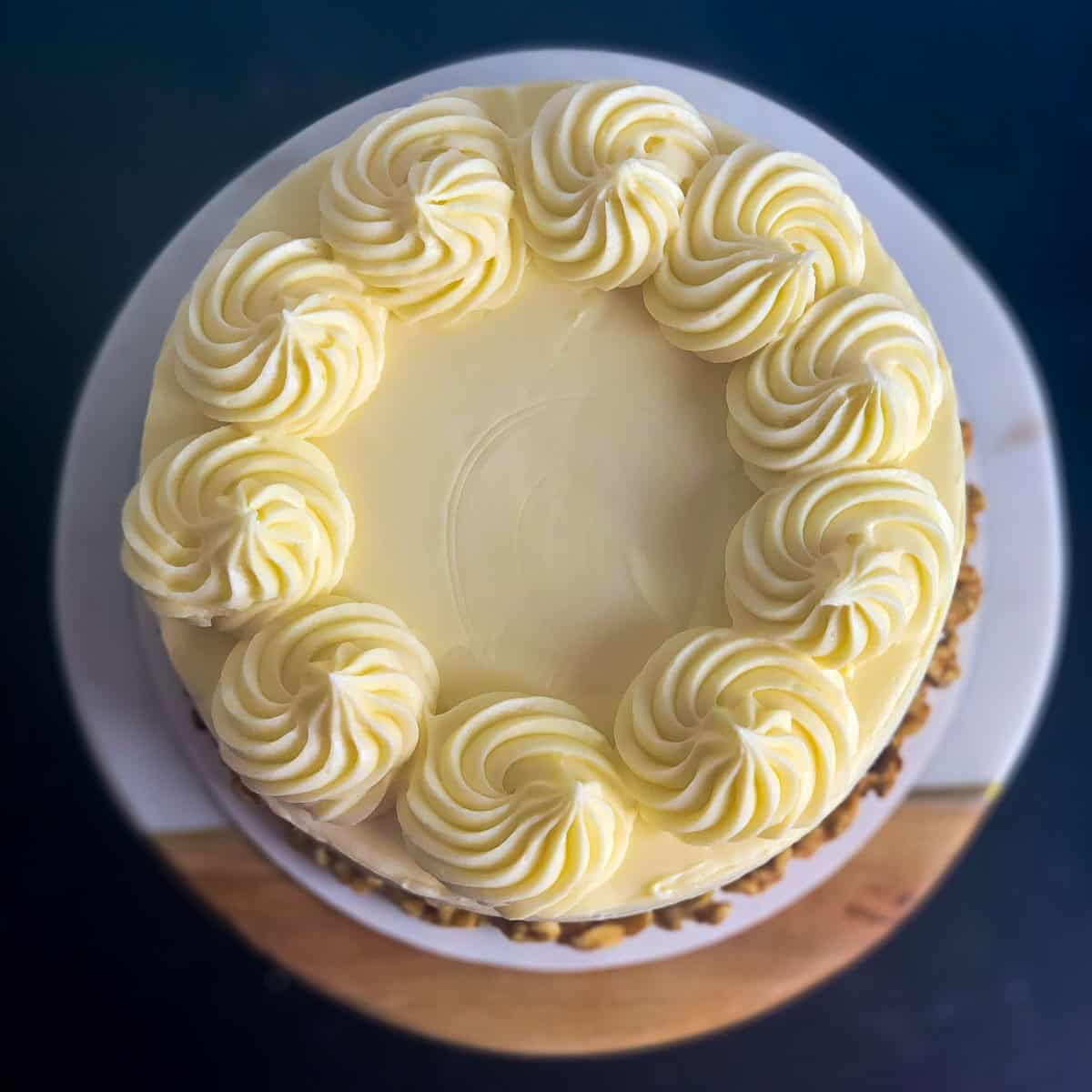 top view of carrot cake with cream cheese frosting and rosette border on black table