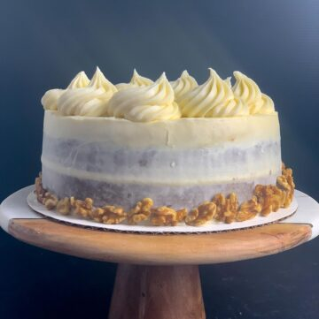 side view of carrot cake with cream cheese frosting, including rosettes, shredded carrot and walnuts, on marble and wood cake stand with black background.
