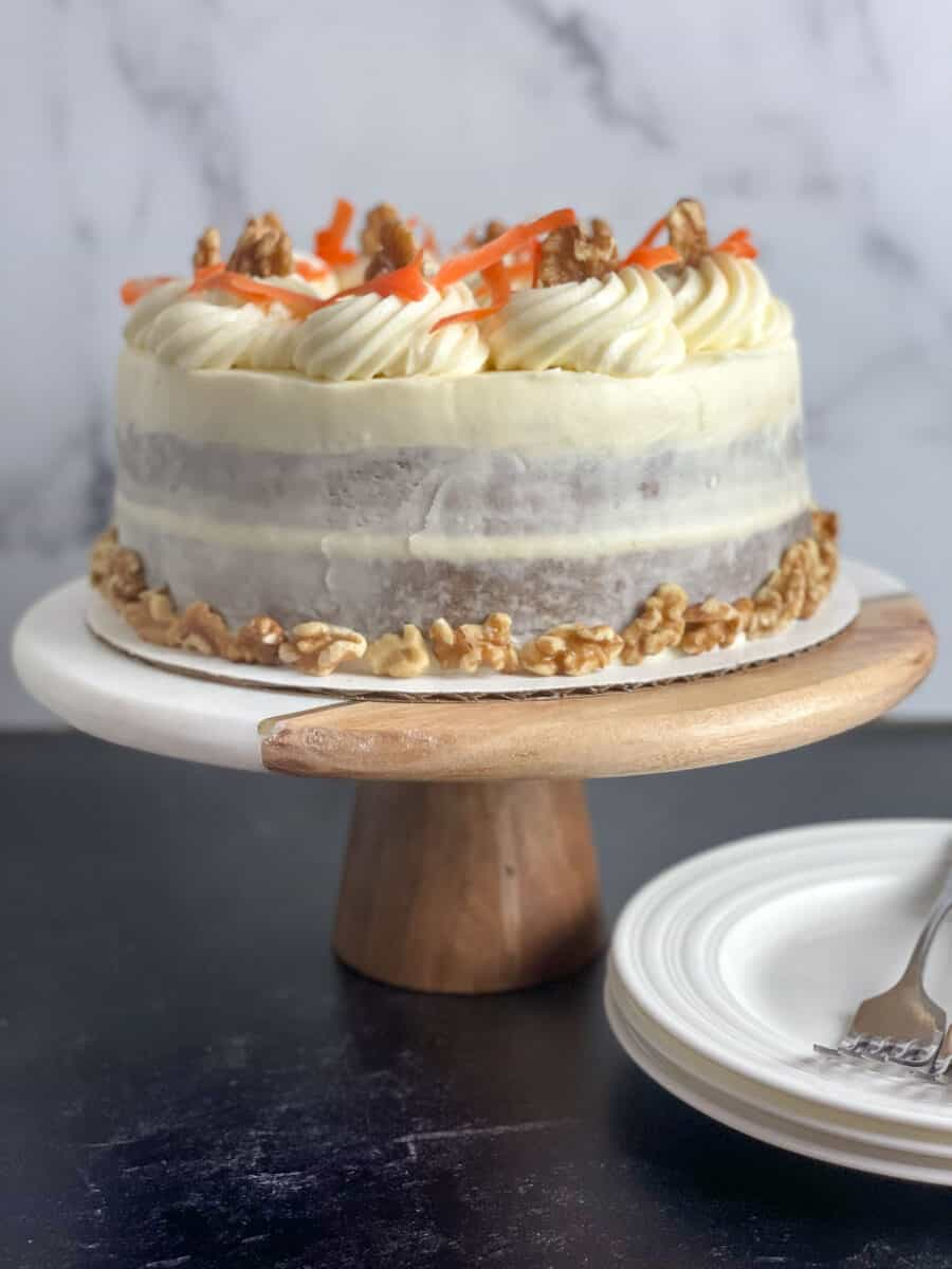 side view of carrot cake with cream cheese frosting, including rosettes, shredded carrot and walnuts, on marble and wood cake stand on black table with 2 dishes and forks. How to Make the Best Carrot Cake Ever