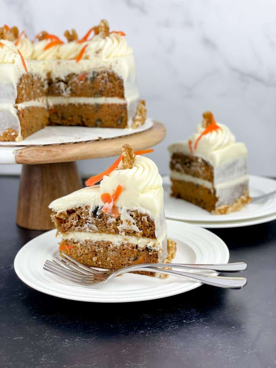 slice of carrot cake on top of 2 stacked dishes with forks and cake in background on cake pedestal, all on black table