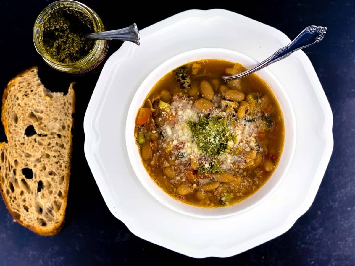 overhead view of minestrone soup in white bowl with pesto and parmesan topping, slice of sourdough bread, and jar of pesto, all on black background.