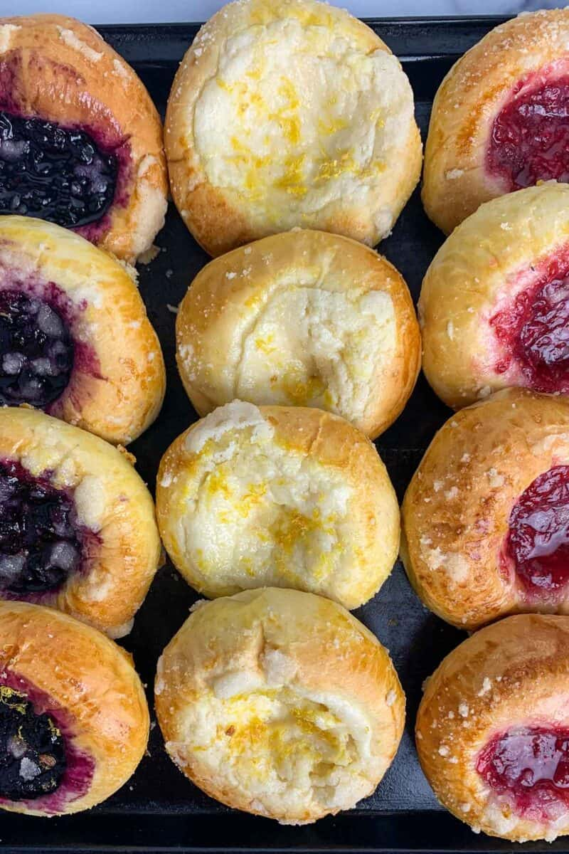 overhead view of 12 baked kolache in blueberry cheese and raspberry on black plate o