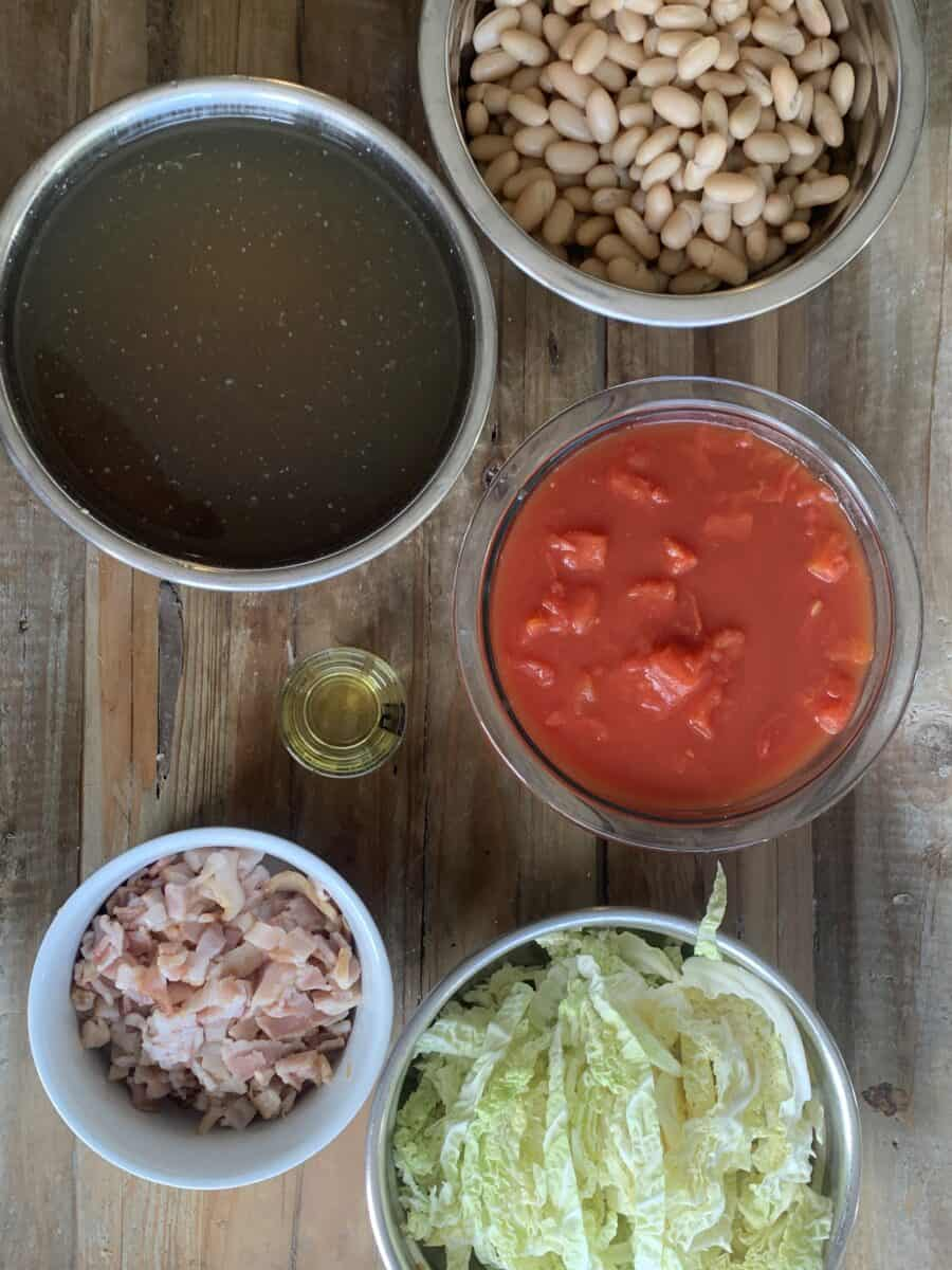 minestrone ingredients, measured out in bowls: cannelloni beans, chicken broth, tomatoes and sauce, olive oil, bacon, sliced cabbage
