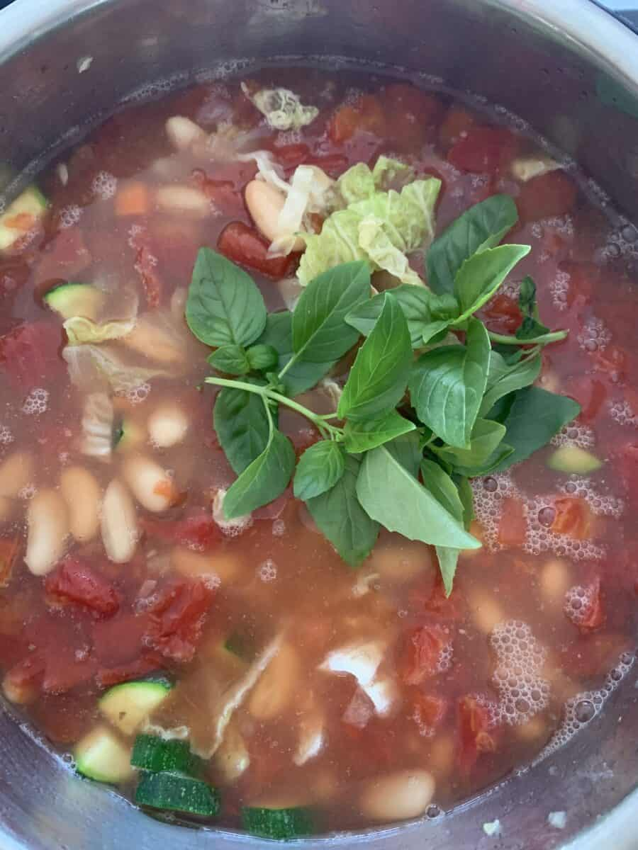 Overhead view of minestrone cooking in pot, topped with fresh basil