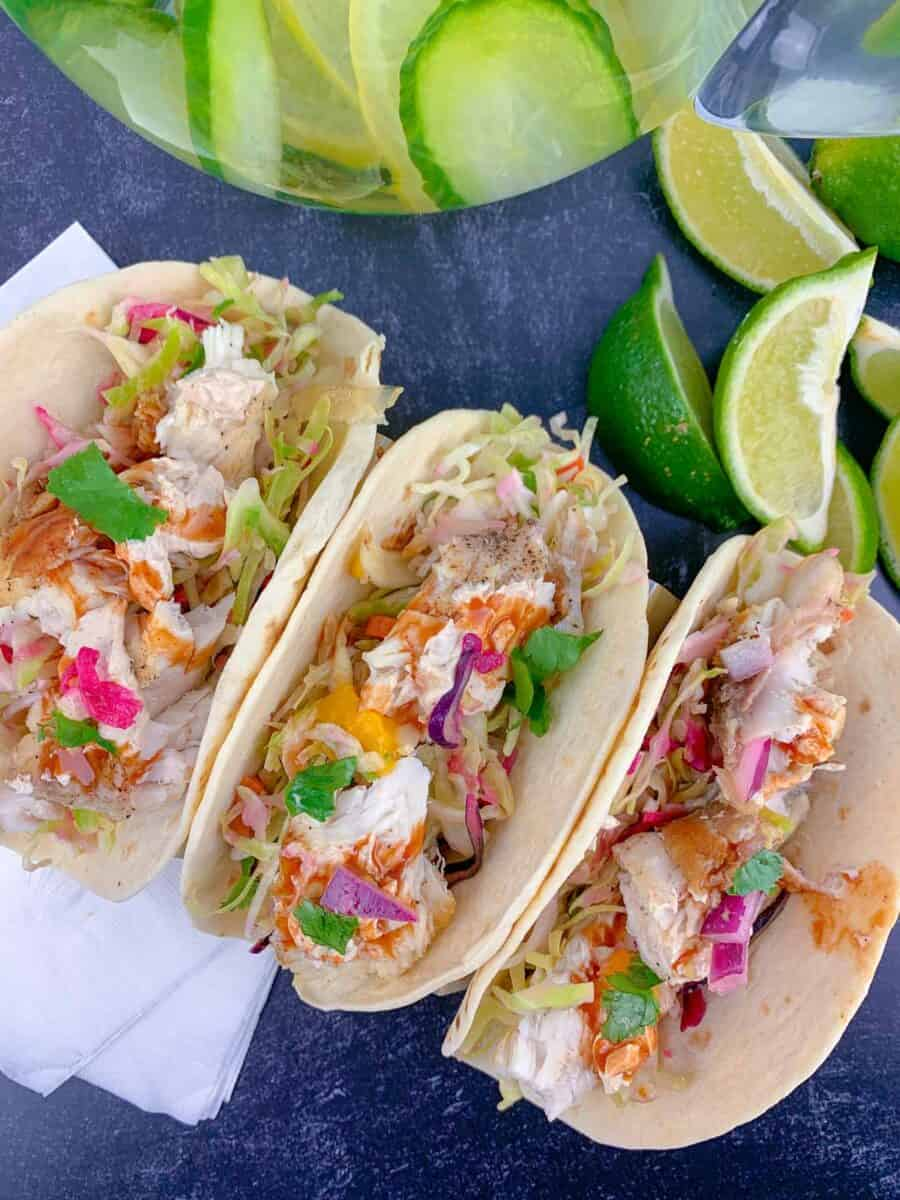 overhead view of three fish tacos on black table with white napkin and lime wedge garnish