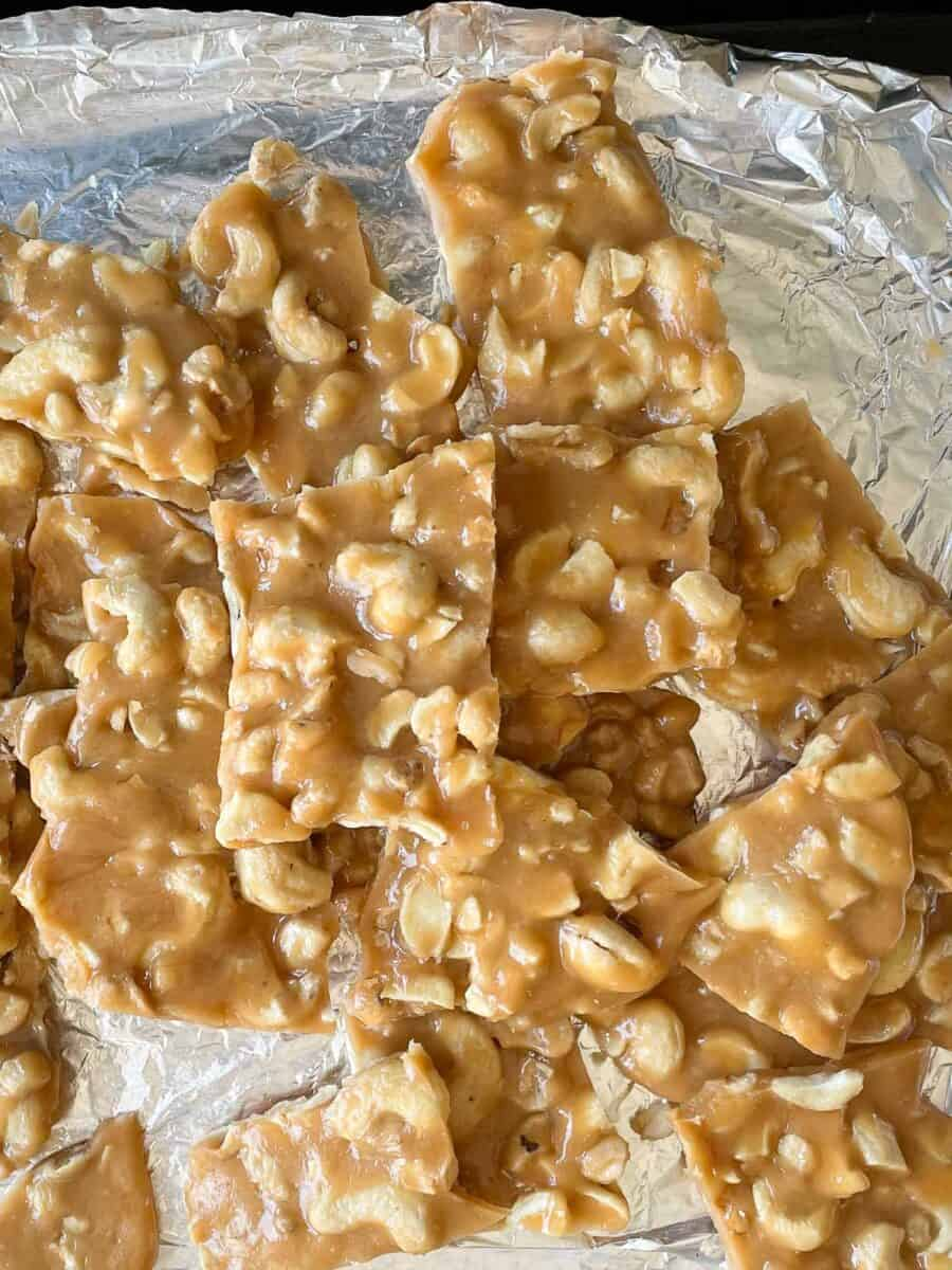 top view of cashew brittle pieces on aluminum foil lined baking sheet