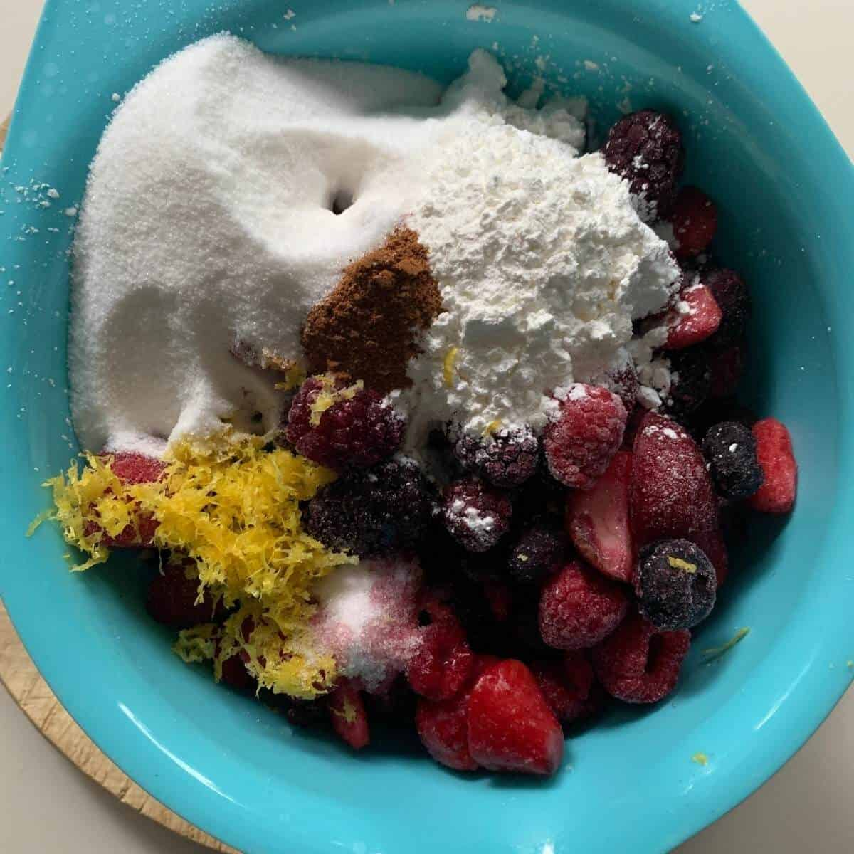 mixed berry pie filling ingredients in blue bowl