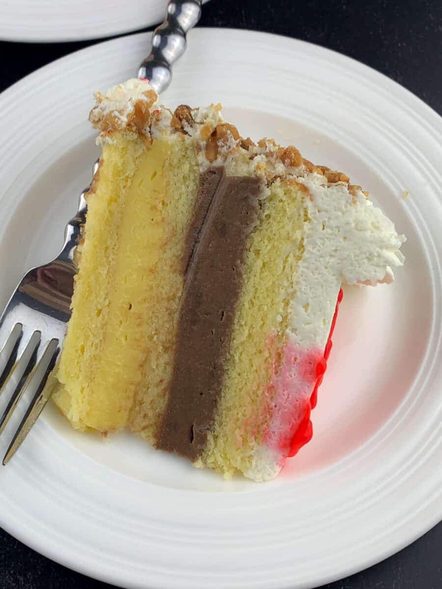 slice of italian rum cake on white plate with fork