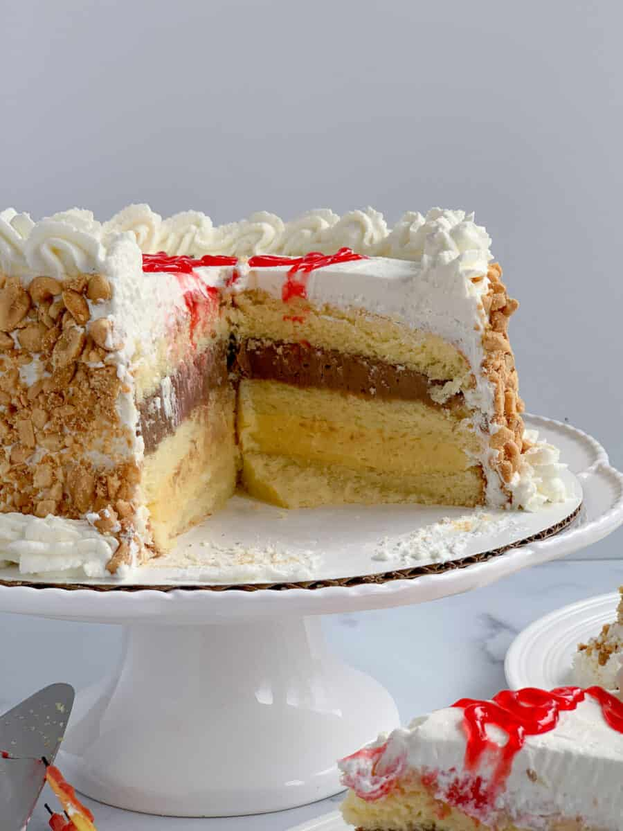 italian rum cake on cake stand with several pieces missing, showing layers of vanilla and chocolate pastry cream