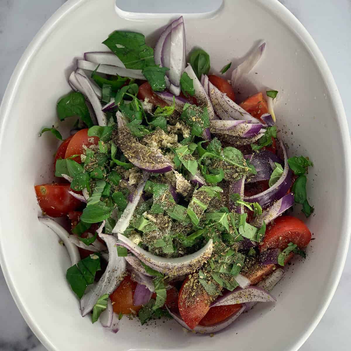 italian tomato salad in white bowl without dressing