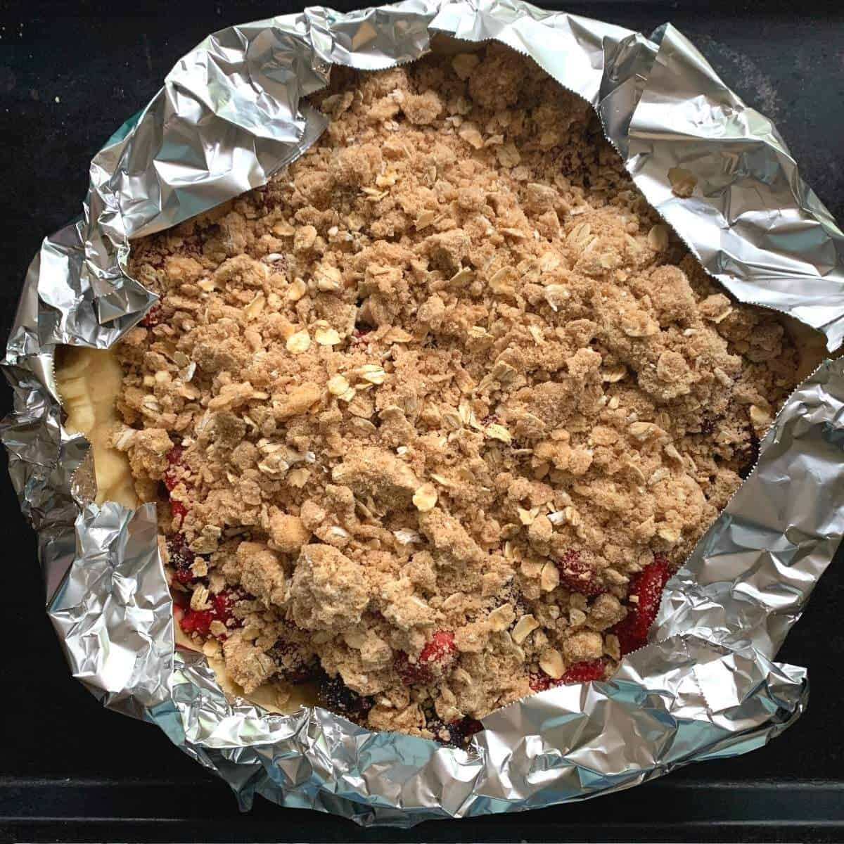 top view of mixed berry pie with crumb topping and aluminum foil covering edges