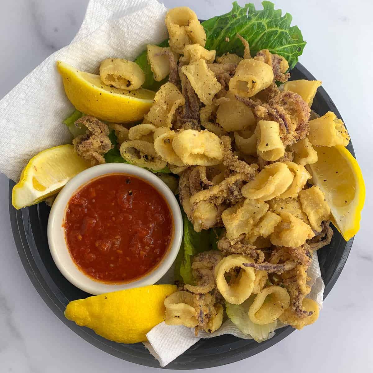 top view of fried calamari with lemon and marinara sauce