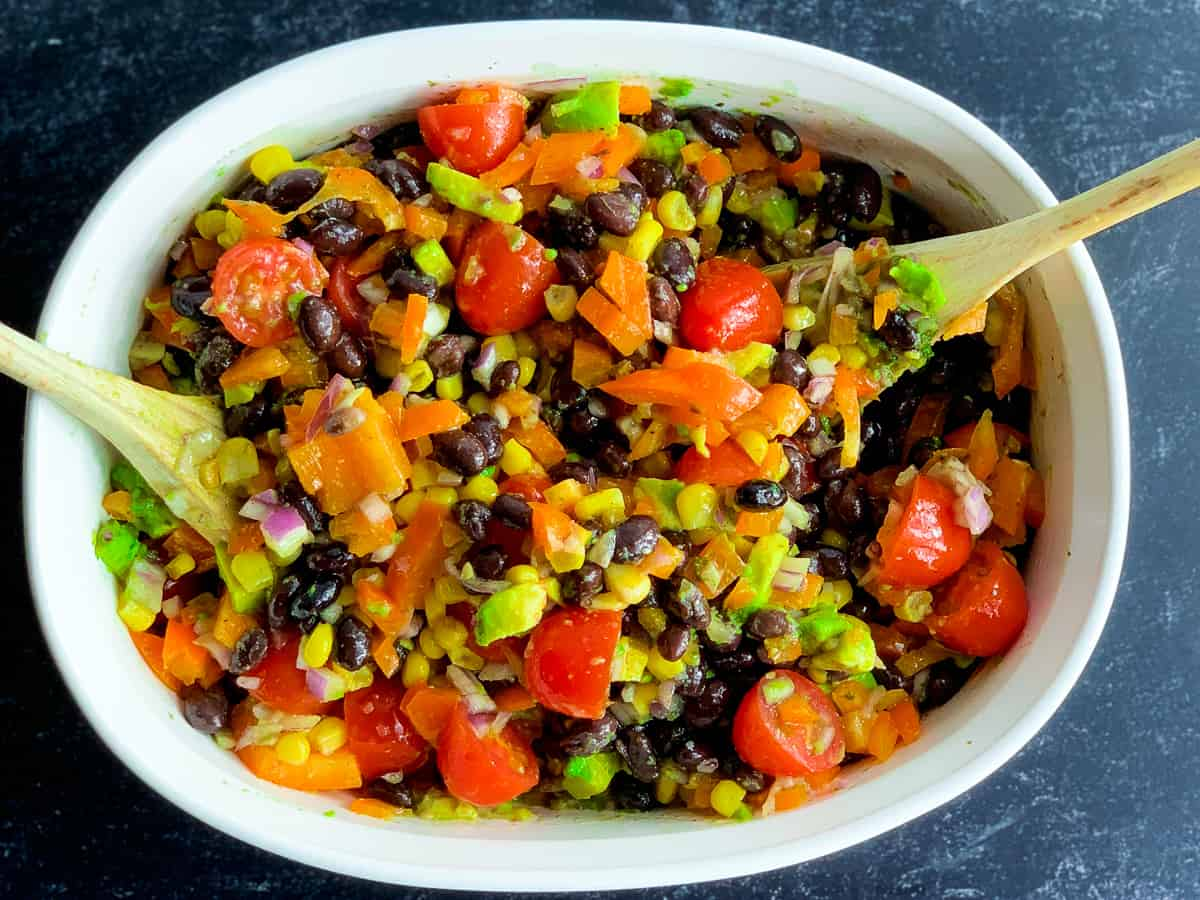 black bean and corn salad in white dish with wooden spoons