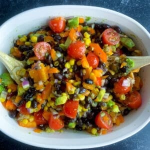 black bean and corn salad in white serving bowl with wooden spoons