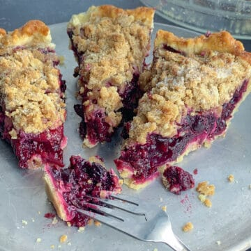 top view of 3 slices of mixed berry pie on silver dish with forks