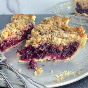 side view of 3 slices of mixed berry pie on silver dish with forks
