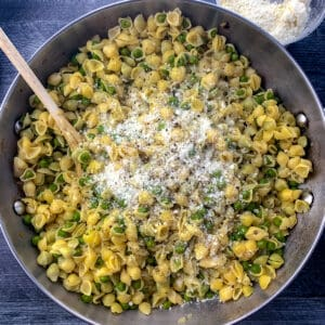 large pan of pasta with peas with wooden on grey table