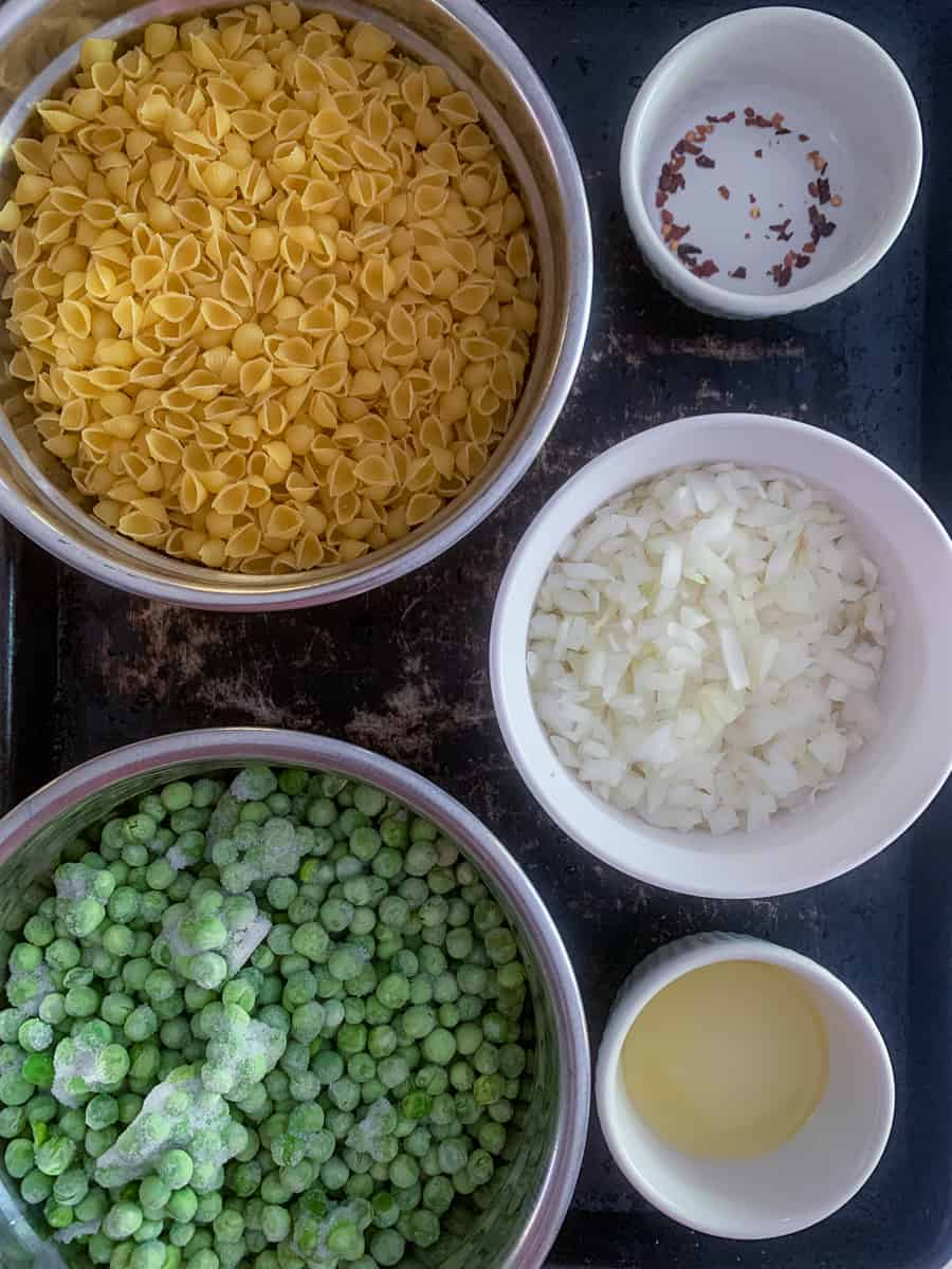 overview of major ingredients: pasta, peas, onion, olive oil and red pepper flakes