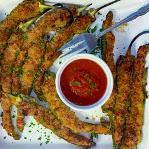 Stuffed Italian long hots on white plate with marinara sauce for dipping