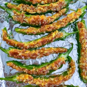 stuffed Italian long hots on aluminum foil ready to be topped with breadcrumbs and baked