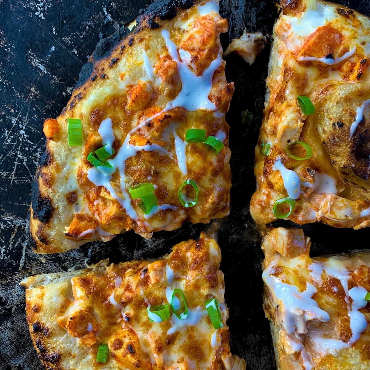 flour slices of buffalo chicken pizza on pizza pan overhead view
