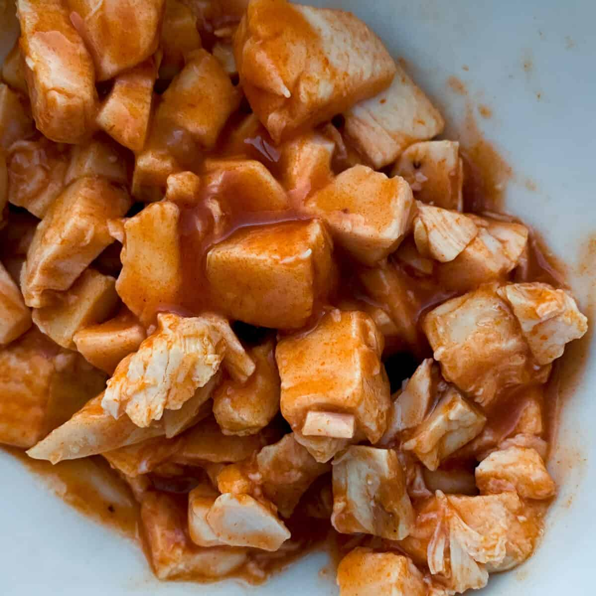 close up view of cubed chicken tossed with hot sauce