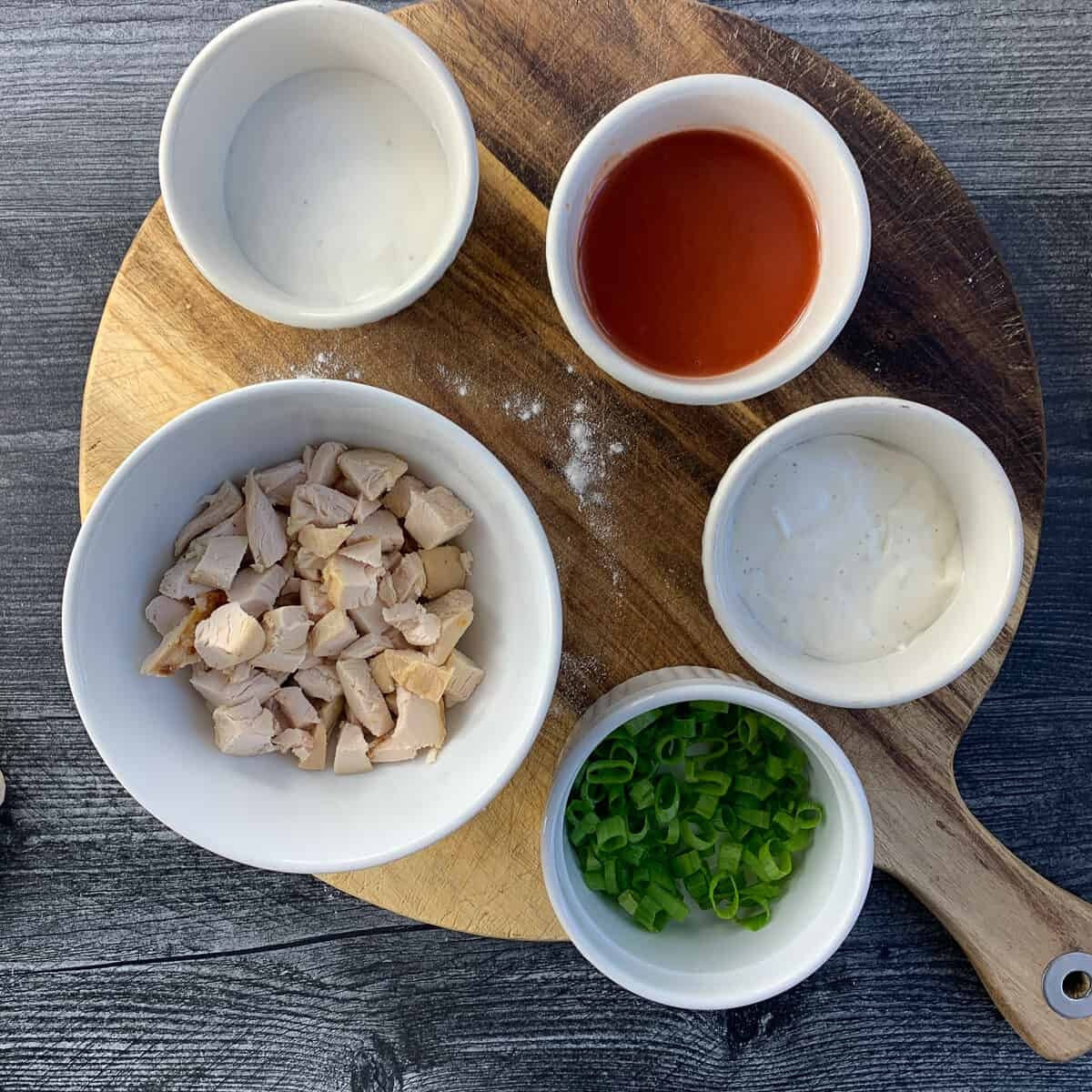Wooden cutting board with small bowls of cubed chicken, ranch dressing, hot sauce, blue cheese dressing and green onions