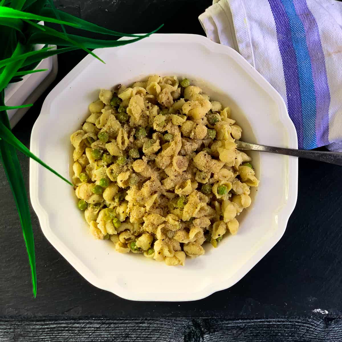 top view of pasta with peas in white bowl with spoon and white purple napkin