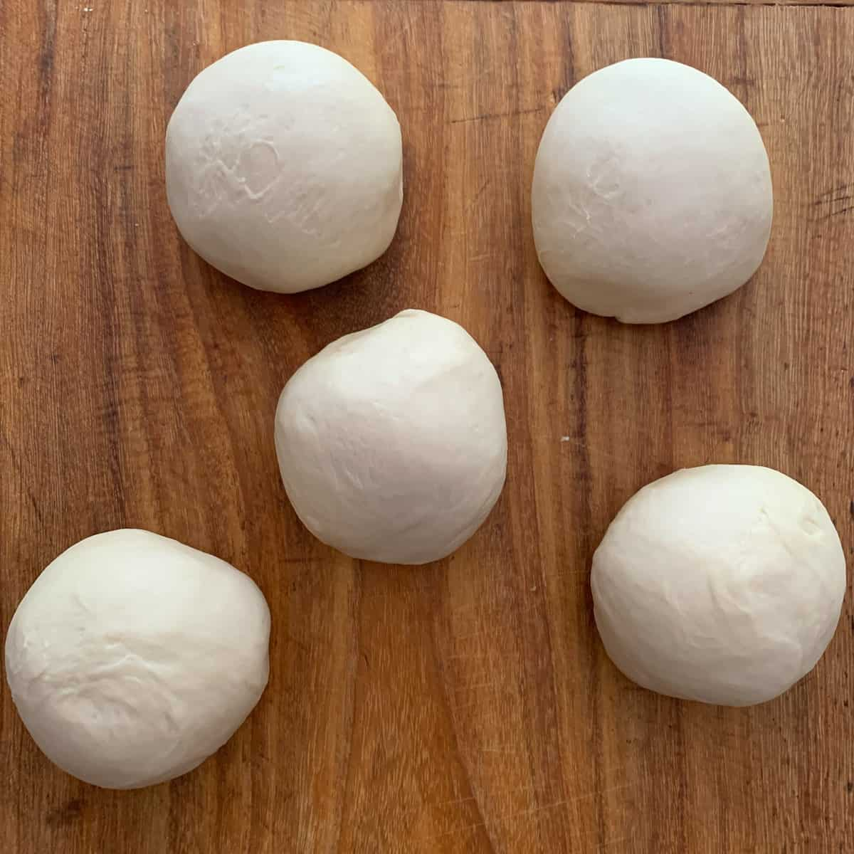 5 balls of dough on wooden board