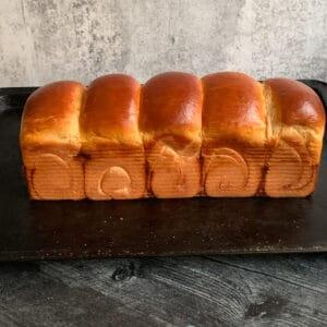 baked shokupan on black baking sheet
