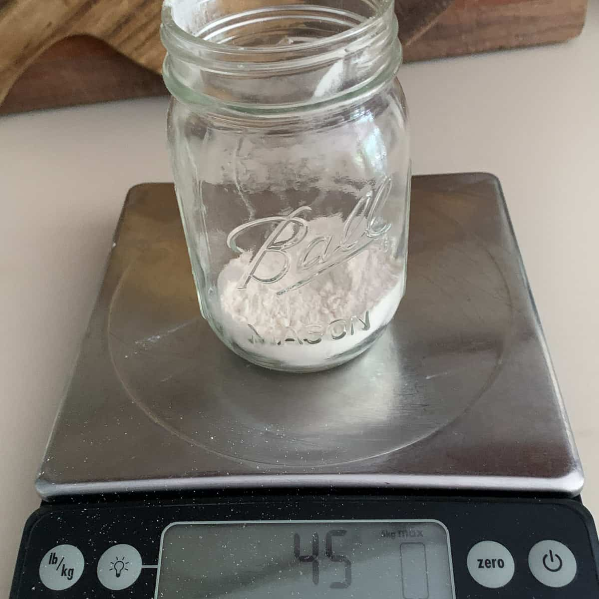 front view of ball jar on scale measuring flour ingredient at 45 grams